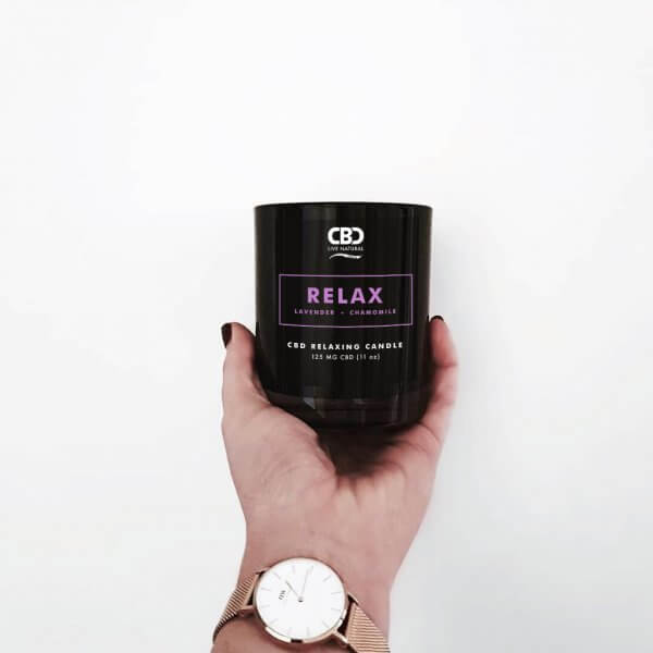 Hand holding Black Tumbler Candle with the words Relax on it